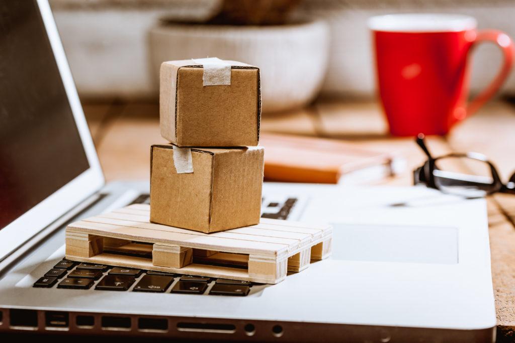 Carton boxes on computer as online shopping logistics concept
